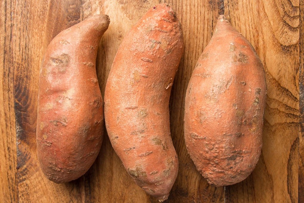 Three Sweet Potatoes on a Wooden Surface