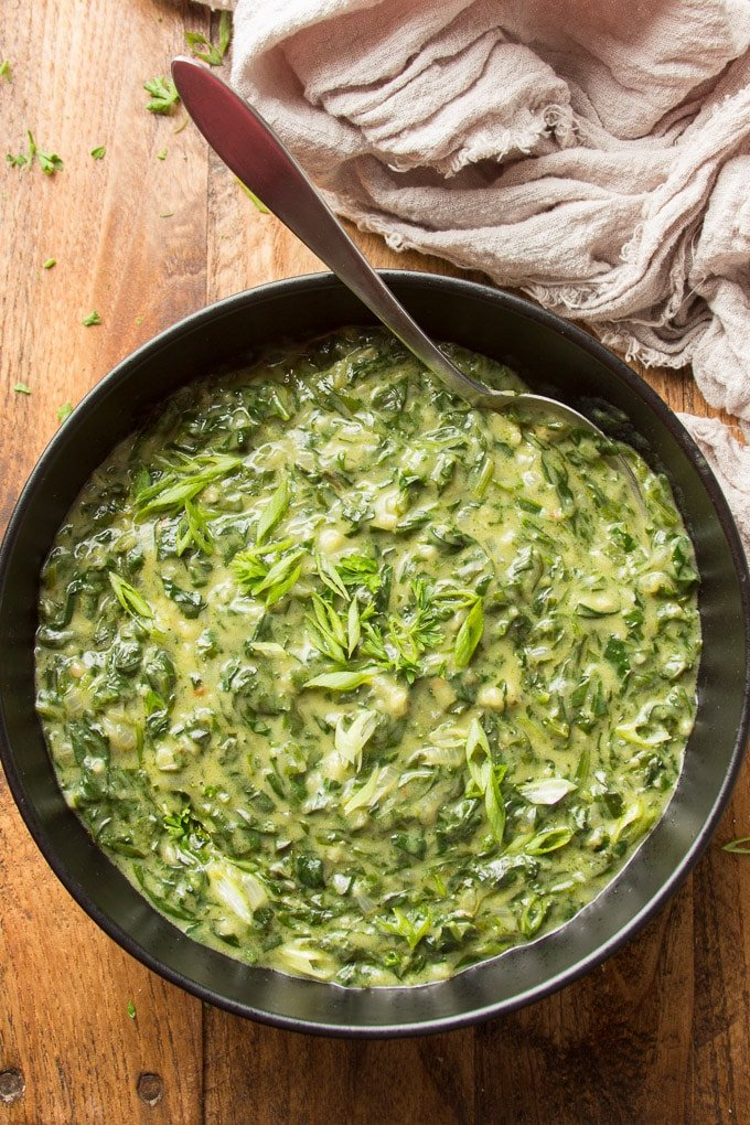 Bowl of Vegan Creamed Spinach with Serving Spoon on a Wood Surface