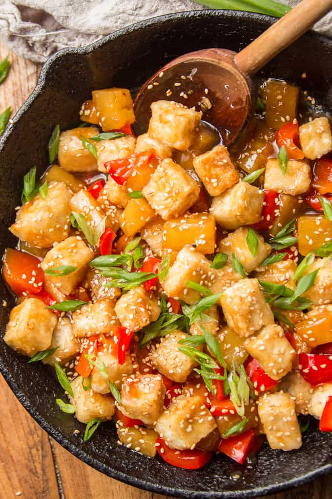 Close Up of Sweet & Sour Tofu in a Skillet with Wooden Spoon