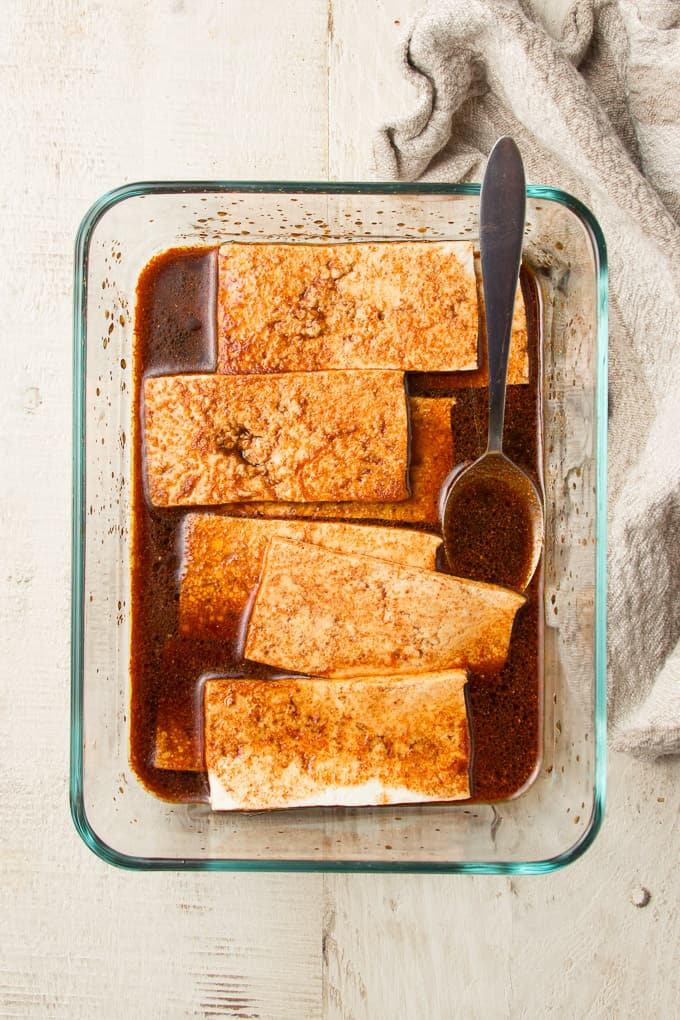 Tofu Strips Marinating in a Glass Dish with Spoon