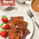 "White Surface Set with Coffee Cup, Baking Sheet, and Dish of Tofu Bacon and Strawberries with Text Overlay Reading ""Tofu Bacon"""