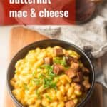 """Bowl of Vegan Butternut Squash Mac & Cheese on a Wooden Surface with Text Overlay Reading """"Spicy Vegan Butternut Squash Mac & Cheese"""""""