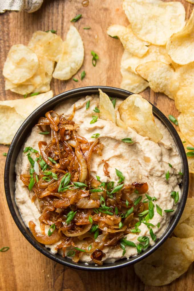 Overhead View of a Bowl of Vegan French Onion Dip Surrounded by Chips on a Wooden Surface