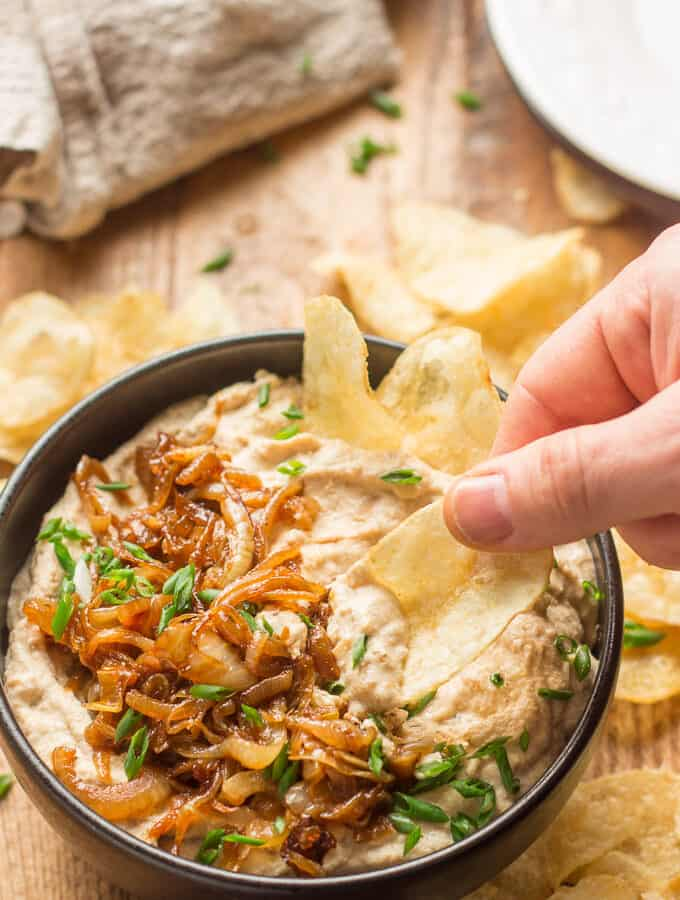 Hand Dipping a Chip into a Bowl of Vegan French Onion Dip