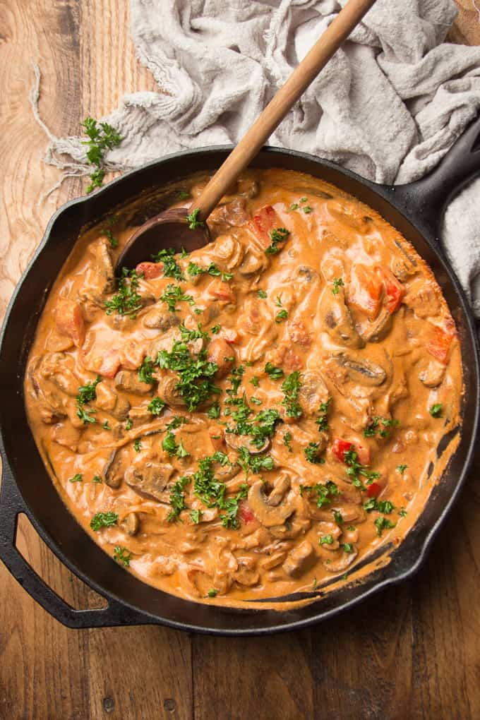 Cast Iron Skillet Filled with Vegan Mushroom Paprikash with Wooden Spoon