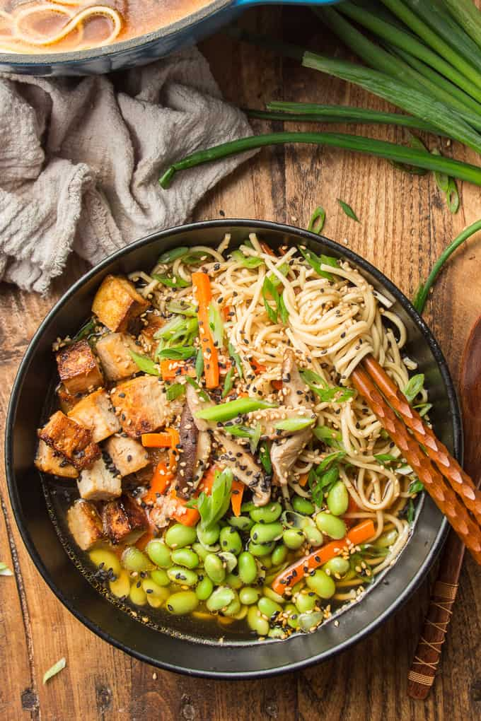 Overhead View of a Bowl of Vegan Ramen on a Wooden Surface, with a Cluster of Noodles Wrapped Around Chopsticks