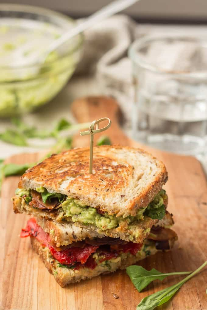 Two Halves of a Grilled Avocado Sandwich Stacked on a Cutting Board