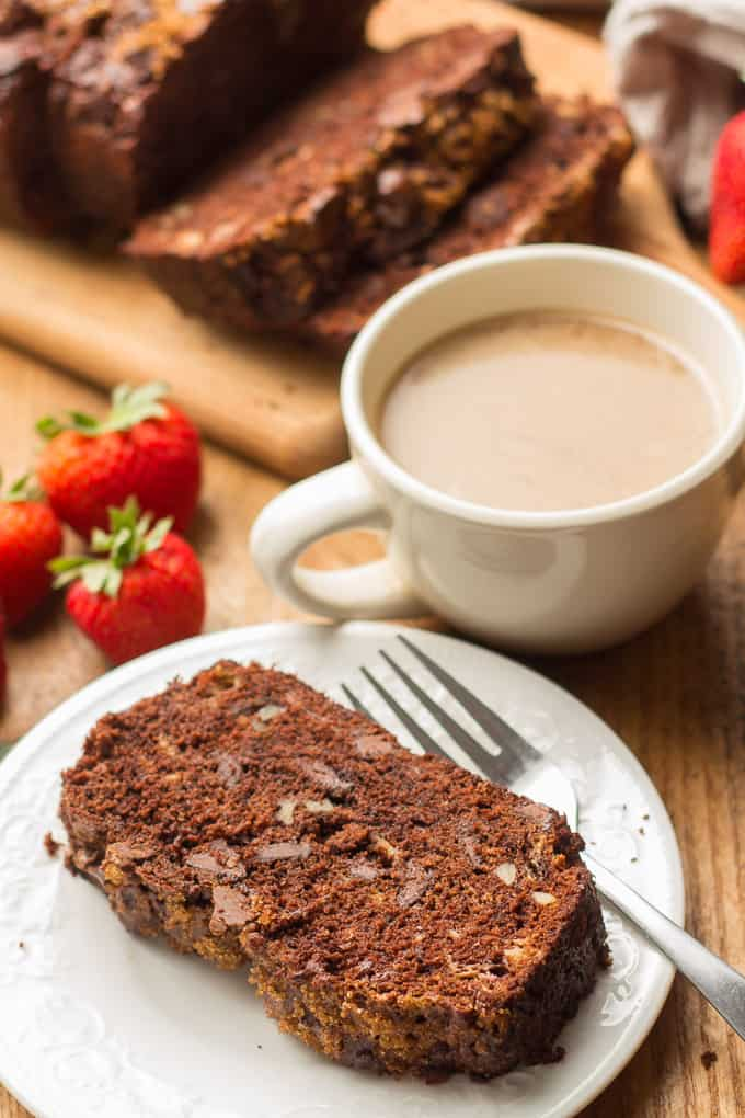 Slice of Vegan Chocolate Banana Bread on a Plate with Coffee Cup and Strawberries in the Background