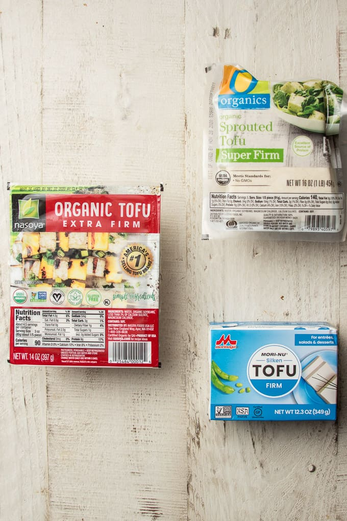 Three Packages of Different Varieties of Tofu on a White Wooden Surface