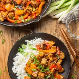 Wooden Table Set with Skillet, Water Glass, and Plate of Tempeh Stir-Fry with Rice