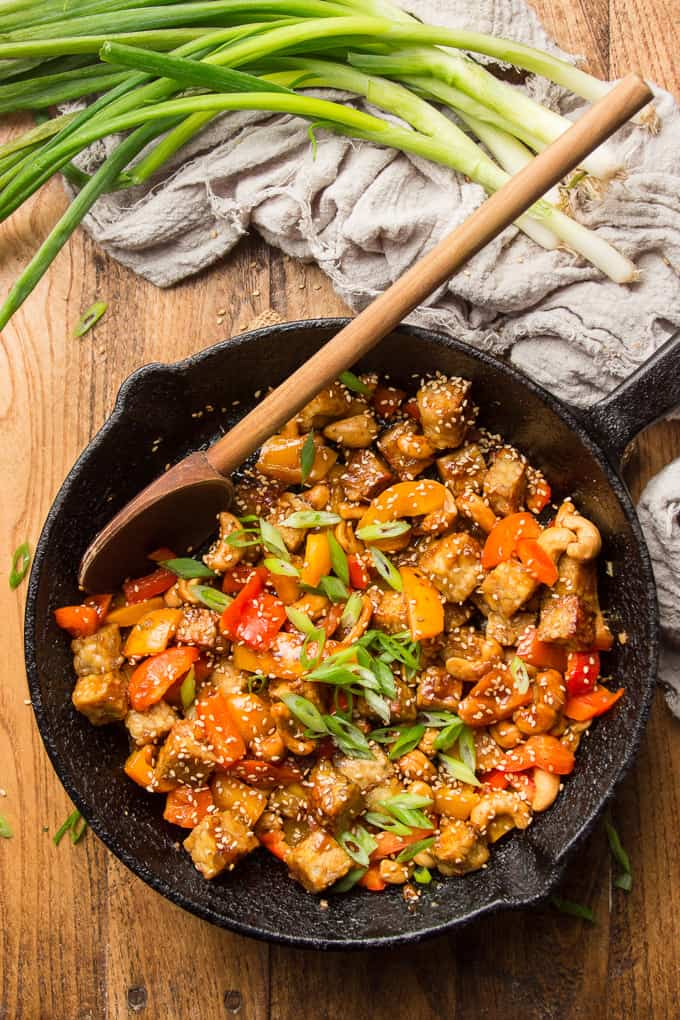 Skillet of Tempeh Stir-Fry with Wooden Spoon on a Wooden Surface