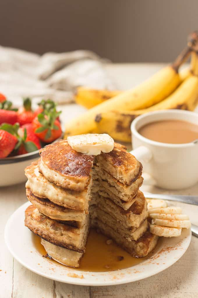 Stack of Vegan Banana Pancakes on a Plate with a Wedge Cut Out