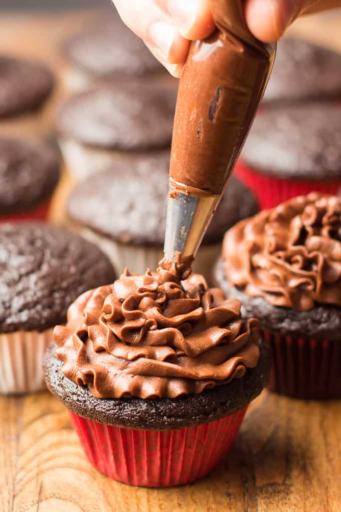Chocolate Frosting Being Piped onto a Vegan Chocolate Cupcake