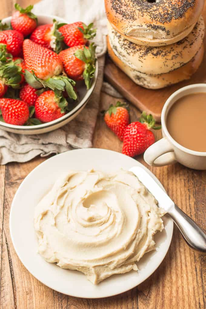Plate of Vegan Cream Cheese with Bowl of Strawberries, Coffee Cup, and Stack of Bagels in the Background