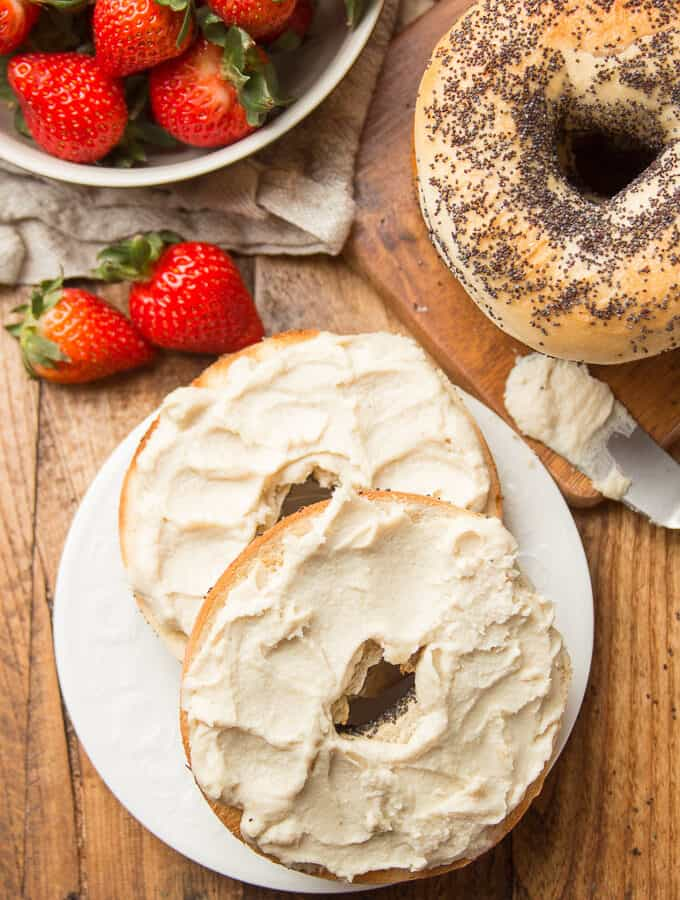 Wooden Table Set with Bowl of Strawberries, Bagels, and Two Bagel Halves on a Plate with Vegan Cream Cheese on Top