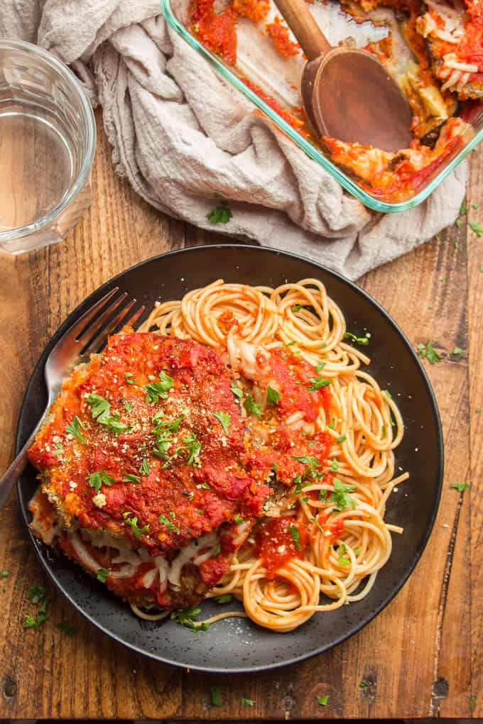 Wooden Table Set with Plate of Vegan Eggplant Parmesan and Pasta, Water Glass and Casserole Dish with Wooden Spoon