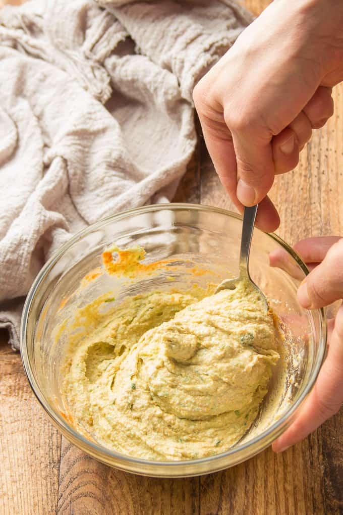 Hand Stirring Ingredients for Vegan Jalapeño Popper Filling Together in a Bowl