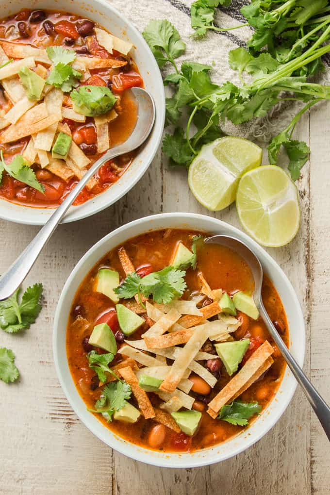 Two Bowls of Vegan Tortilla Soup on a White Wooden Surface with Lime Wedges and Bunch of Fresh Cilantro