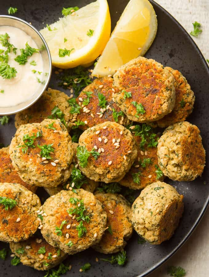Baked Falafels Topped with Sesame Seeds and Parsley, with Hummus and Lemon Slices on the Side