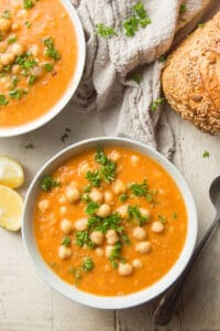 White Wooden Surface Set with Two Bowls of Chickpea Soup, Loaf of Bread and Lemon Wedges