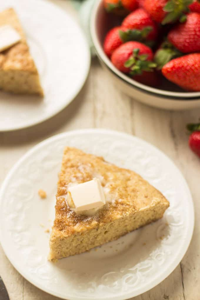 Slice of Vegan Cornbread on a Plate with Bowl of Strawberries in the Background