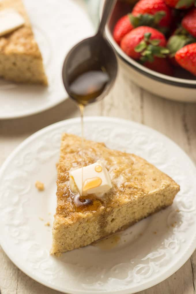 Spoon Drizzling Maple Syrup Over a Slice of Vegan Cornbread