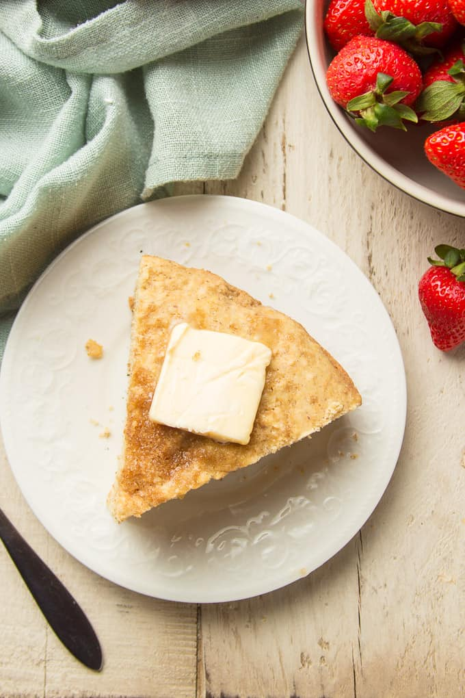 White Wooden Surface Set with Slice of Vegan Cornbread on a Plate, Bowl of Strawberries, and Napkin