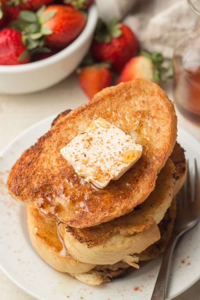 Close up of a Stack of Vegan French Toast on a Plate with Butter and Maple Syrup on Top