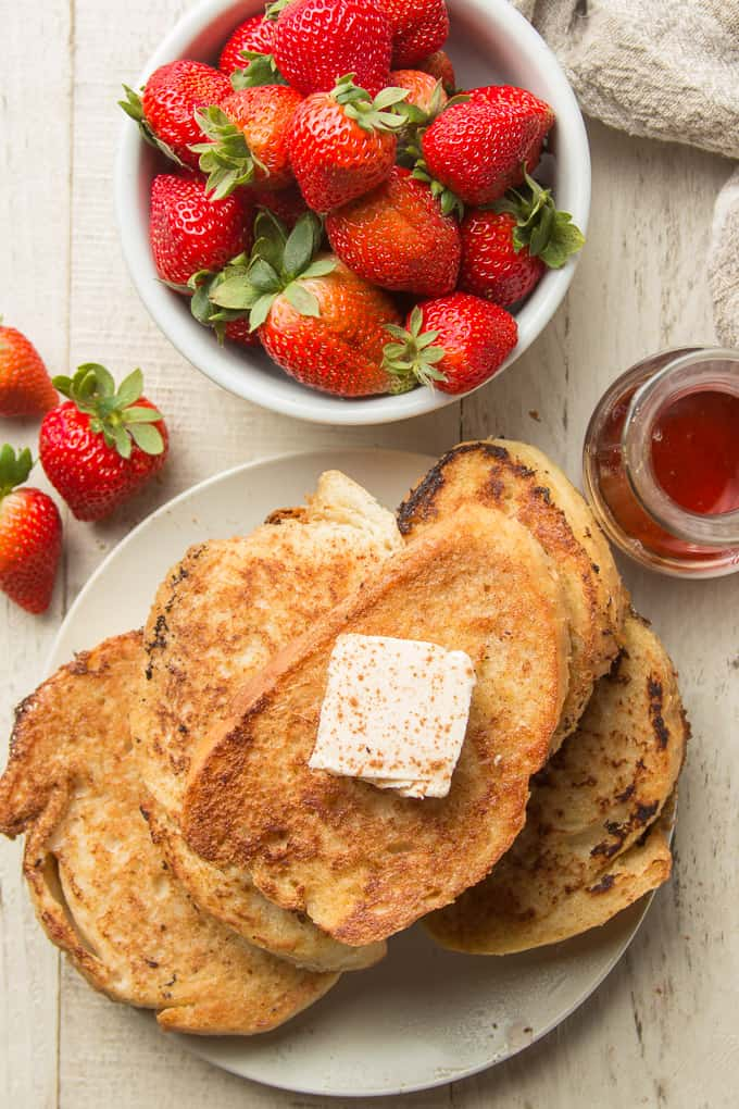 White Wooden Surface Set with Plate of Vegan French Toast, Bowl of Strawberries, and Syrup Decanter