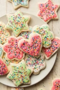 Vegan Sugar Cookies Topped with Colored Frosting and Sprinkles on a Plate