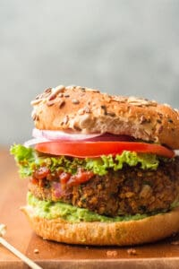 Close Up of a Black Bean Burger on a Bun with, Lettuce, Tomato, Onion, and Avocado