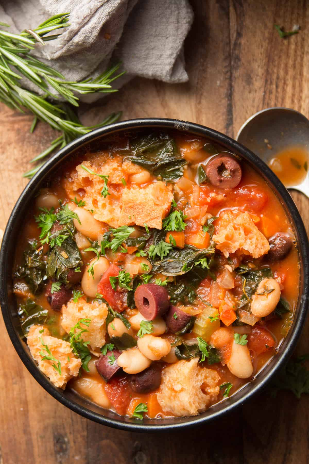 Bowl of Ribollita on a Wooden Surface with Spoon on the Side