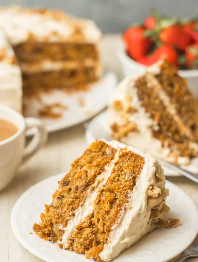 Slice of Vegan Carrot Cake on a Plate with Additional Slices, Coffee Cup and Strawberries in the Background