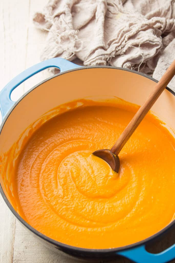 Pot of Carrot Soup with a Wooden Spoon
