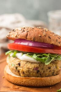 Close Up of a Greek Chickpea Burger Topped with Mayonnaise, Arugula, Lettuce and Red Onion