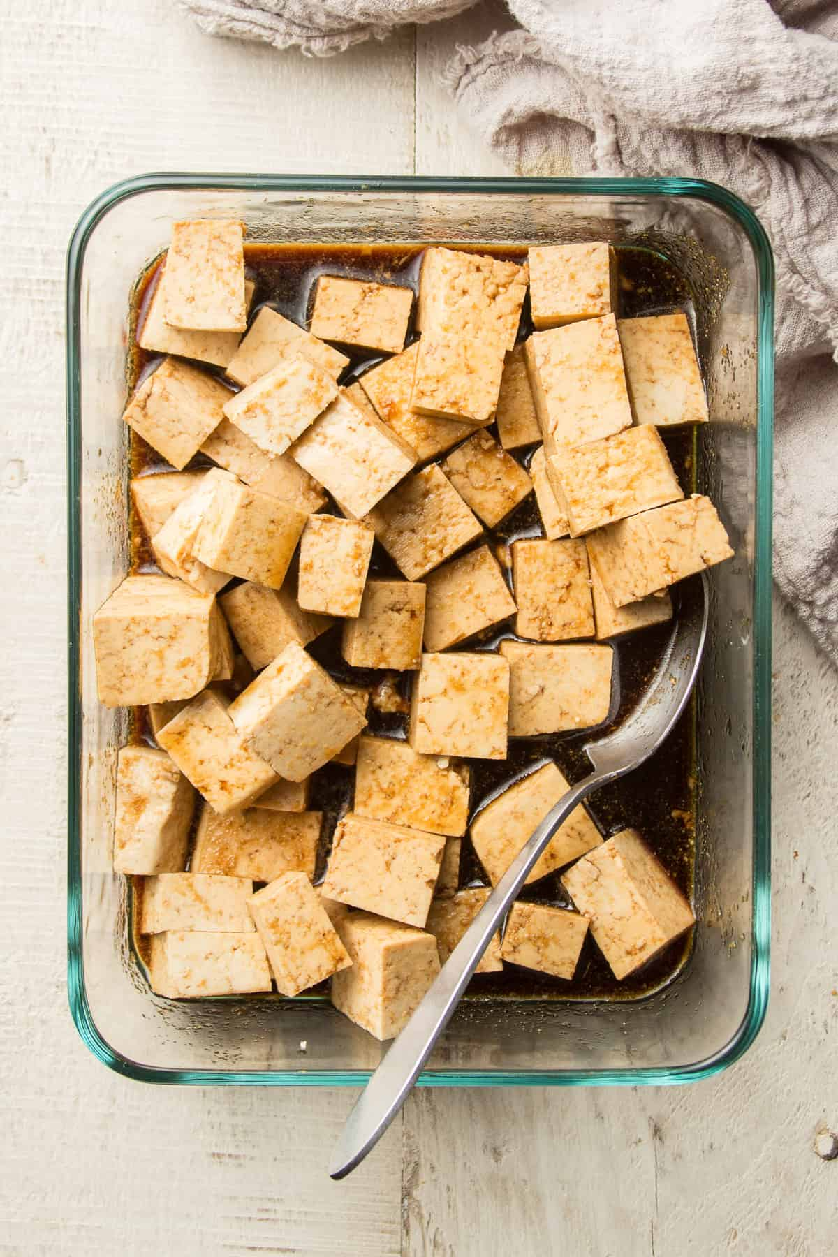 Tofu Marinating in a Glass Dish with Spoon