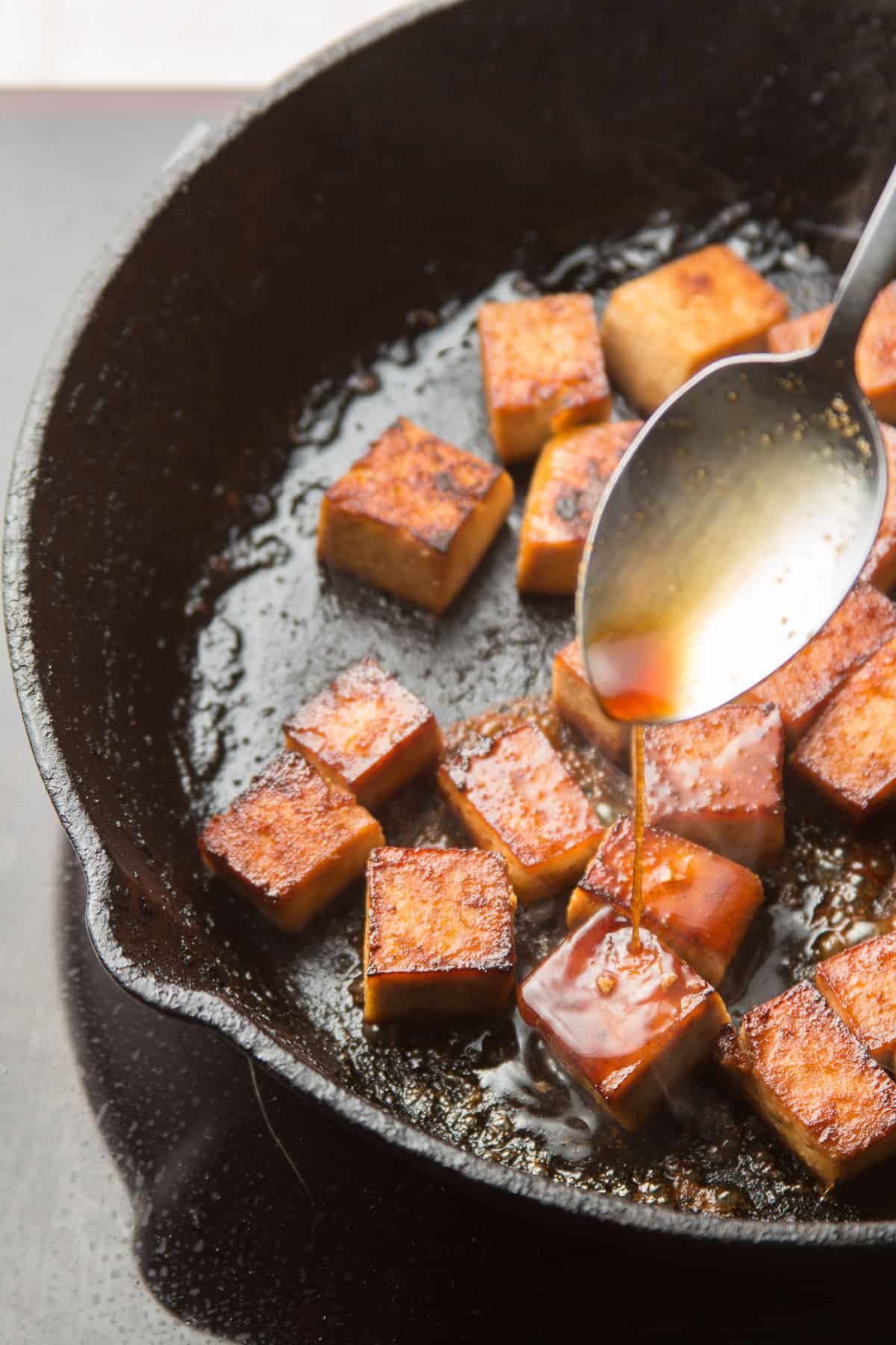 Spoon Drizzling Marinade Over Tofu Sizzling in a Skillet
