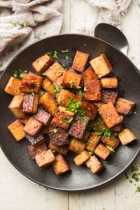 Plate of Marinated Tofu with Herbs on Top and Spoon on the Side