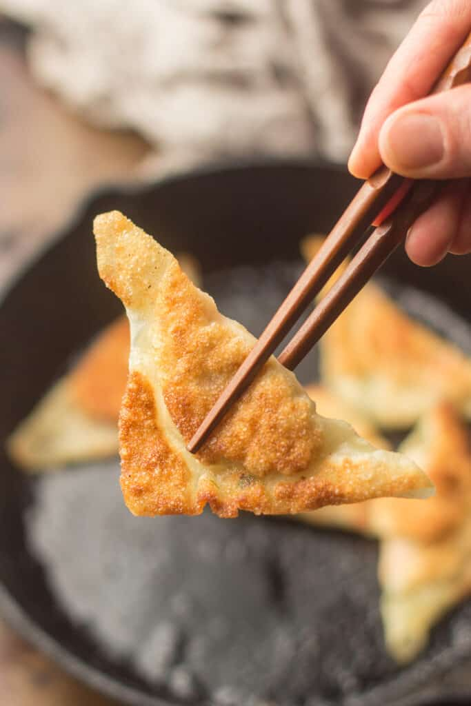 Close Up of a Tofu Dumpling Held Between Two Chopsticks