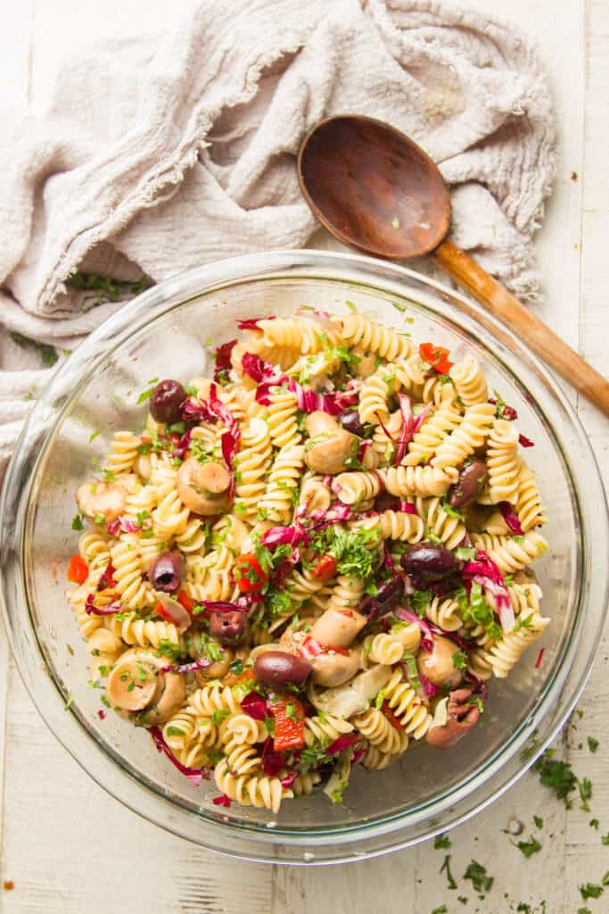 Bowl of Vegan Pasta Salad on a White Wood Surface with Spoon and Cloth on the Side