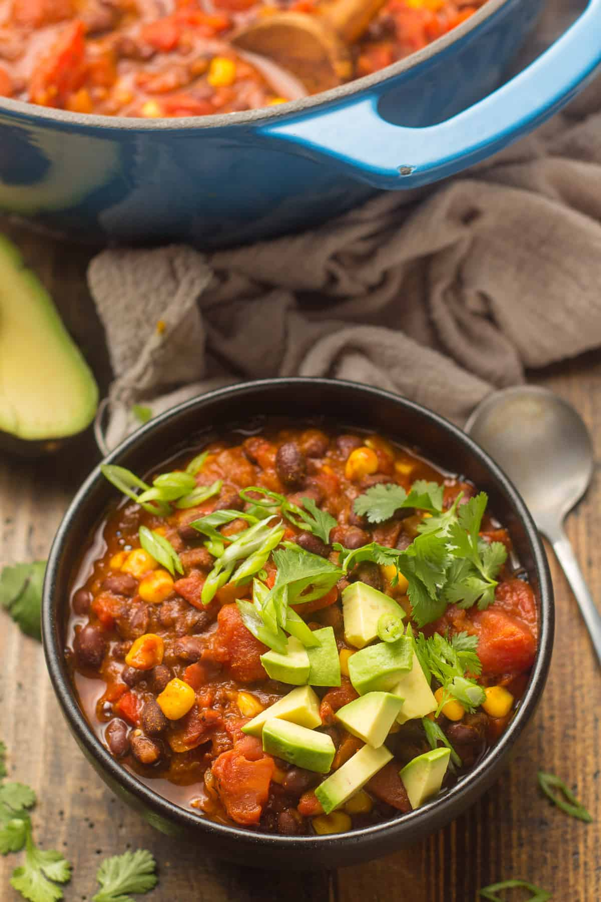 Bowl of Black Bean Chili with Spoon on the Side and Pot in the Background