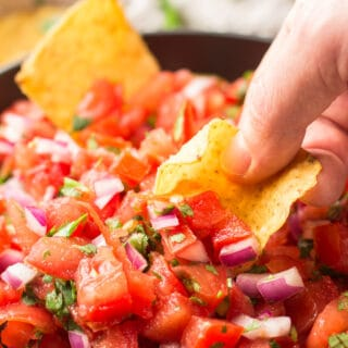 Close Up of Hand Dipping Chip in Pico de Gallo