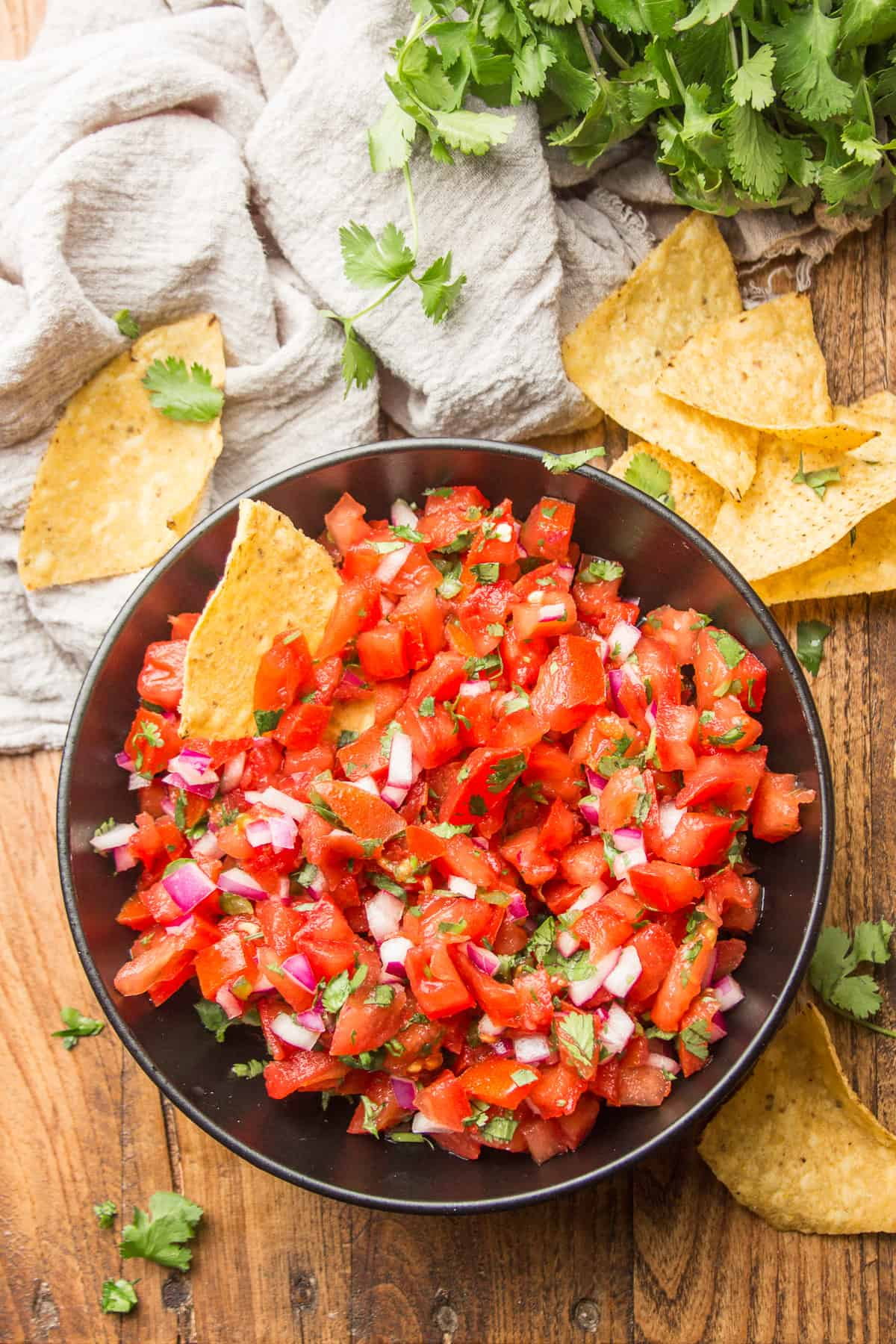 Wooden Surface Set with Bunch of Cilantro, Chips, and Bowl of Pico de Gallo
