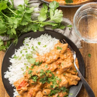 Wooden Table Set with Skillet, Water Glass, and Plate of Vegan Butter Chicken