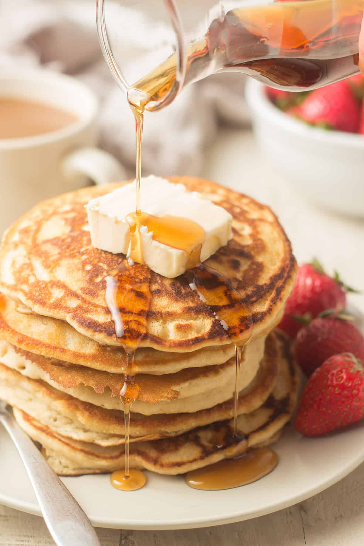 Hand Drizzling Maple Syrup Over a Stack of Vegan Pancakes