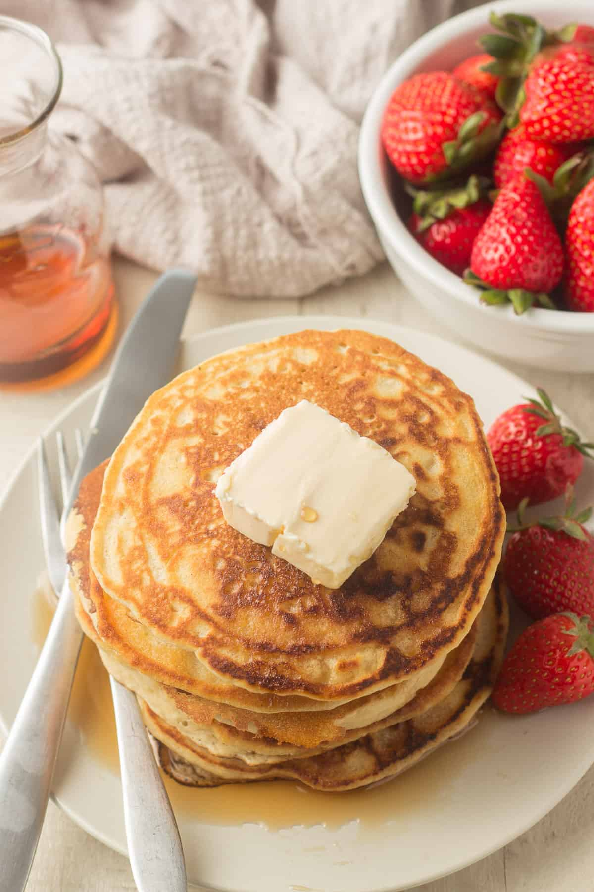 Stack of Vegan Pancakes on a Plate with Butter and Strawberries