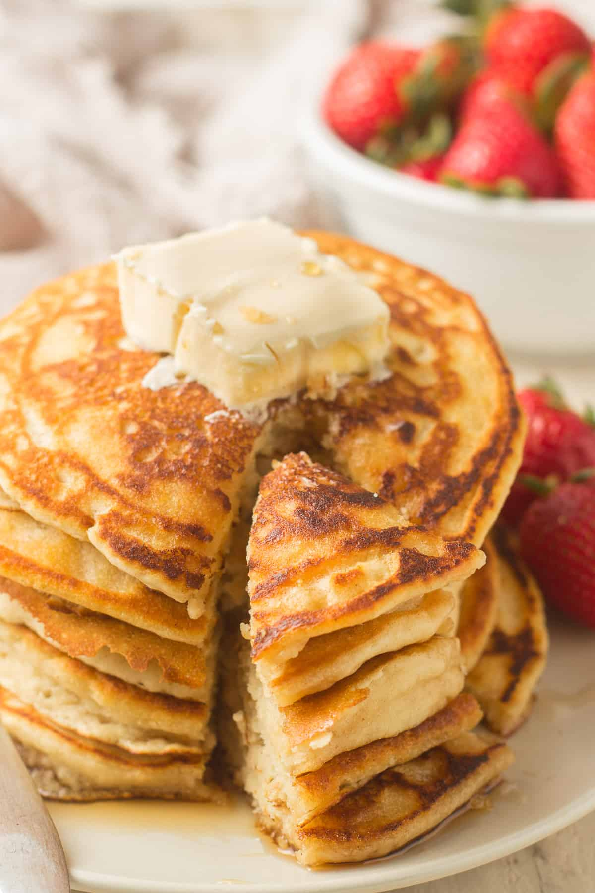 Stack of Vegan Pancakes with Wedge Cut out, Bowl of Strawberries in the Background