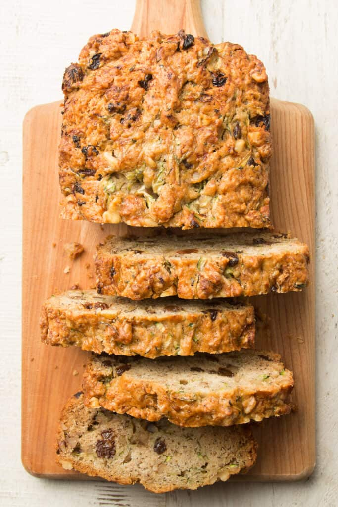 Partially Sliced Loaf of Vegan Zucchini Bread on a Cutting Board