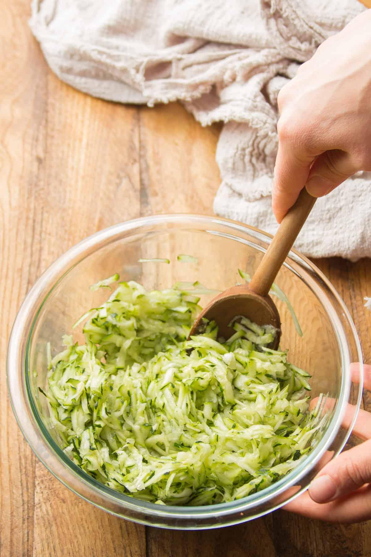 Hand Stirring Salt into Shredded Zucchini in a Bowl