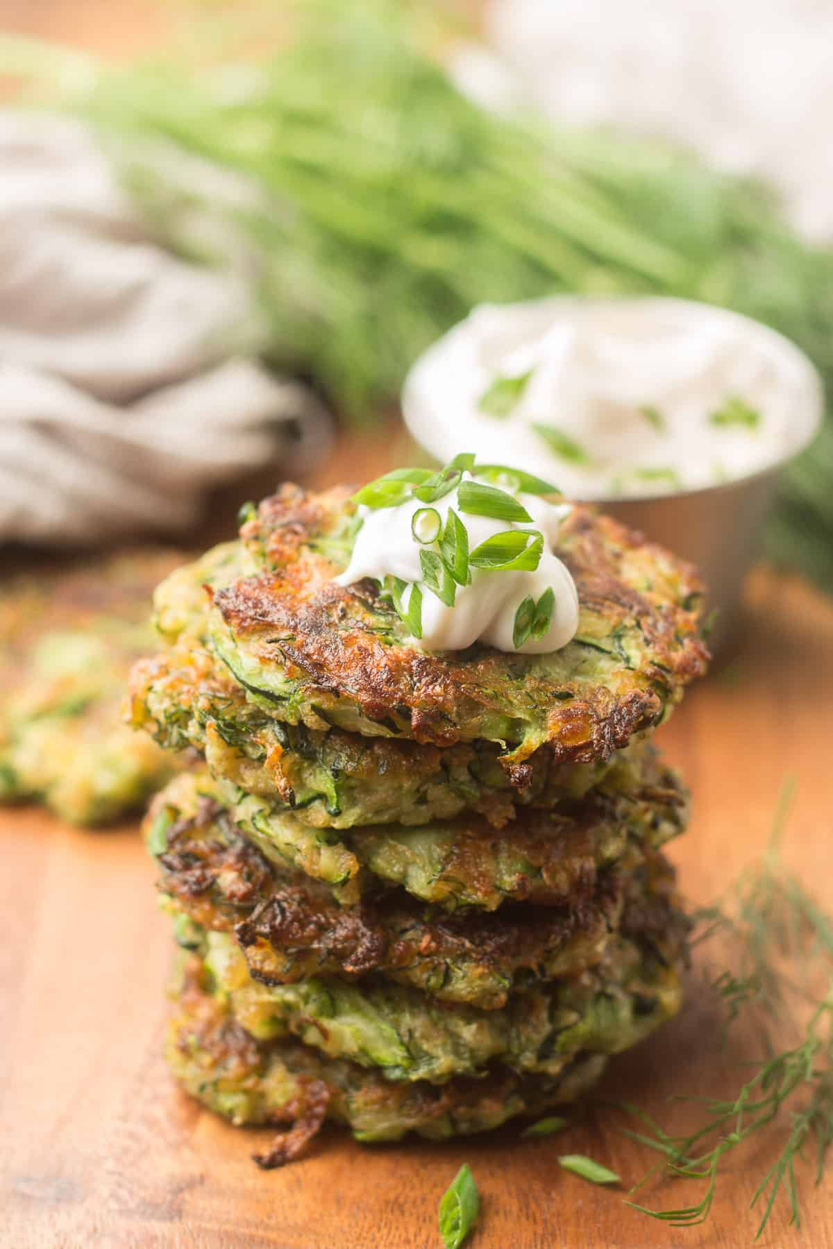 Stack of Vegan Zucchini Fritters with Dish of Cashew Cream and Bunch of Dill in the Background